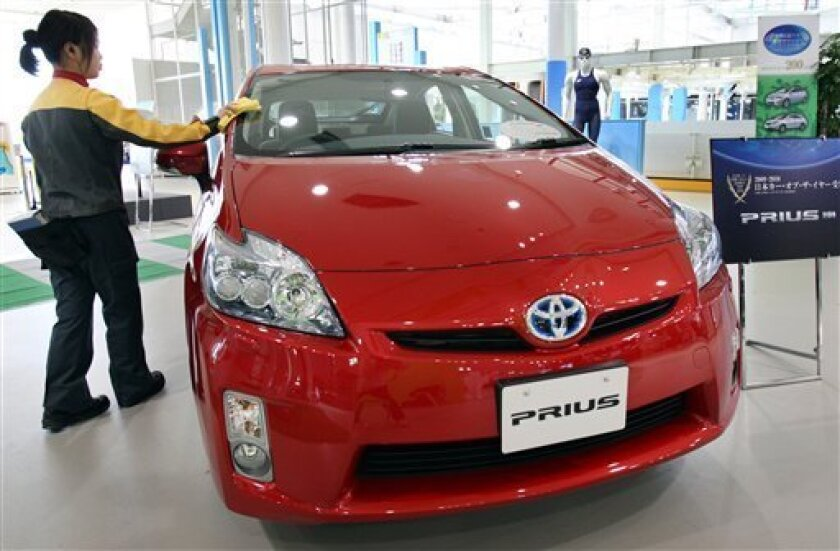 FILE - In this Jan. 8, 2010 file photo, an employee polishes Toyota Motor Corp.'s Prius, which is called 2010 Prius in the U.S., on display at the automaker's showroom in Tokyo. An auto industry group said on Tuesday, Jan. 11, 2011, Prius hybrid is the top-selling vehicle in Japan for 2010 with annual sales hitting an all-time high. (AP Photo/Koji Sasahara, File)