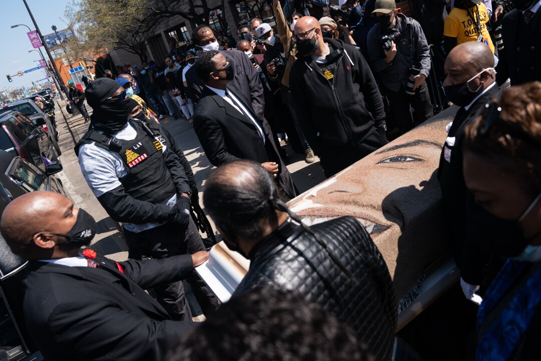 People in masks surround a casket bearing the image of a smiling young man