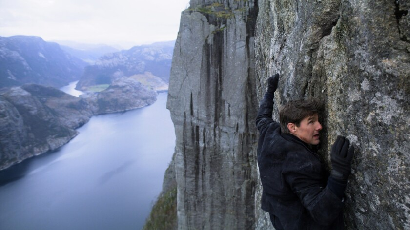 Tom Cruise clings to the side of a mountain