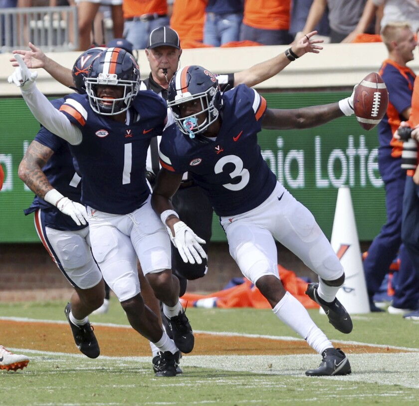 Virginia's Nick Grant (1) celebrates an interception by teammate Anthony Johnson (3) during an NCAA college football game against Illinois, Saturday, Sept. 11, 2021, at Scott Stadium in Charlottesville, Va. (Andrew Shurtleff/The Daily Progress via AP)