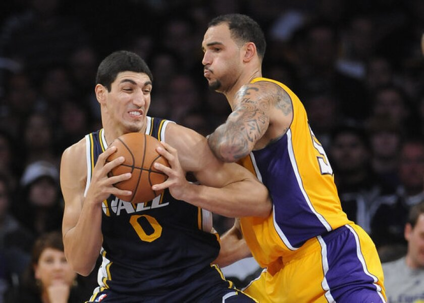 Lakers rookie center Robert Sacre tries to hold his position as Jazz center Enes Kanter works in the post during an exhibition season game.