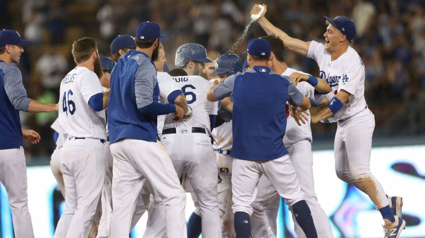 LOS ANGELES, CA, THURSDAY, JULY 6, 2017 - Dodgers teammates mob Chris Taylor after he singled to win