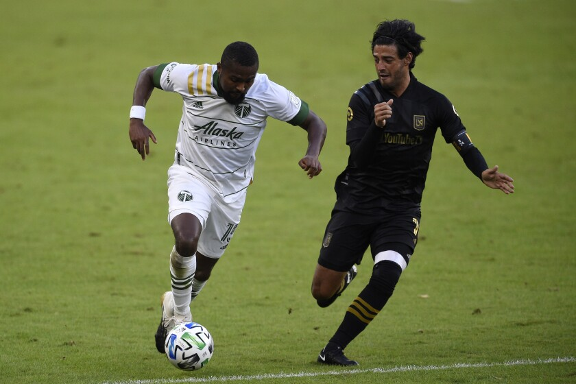 Portland Timbers defender Chris Duvall, left, moves the ball while pressured by LAFC forward Carlos Vela.