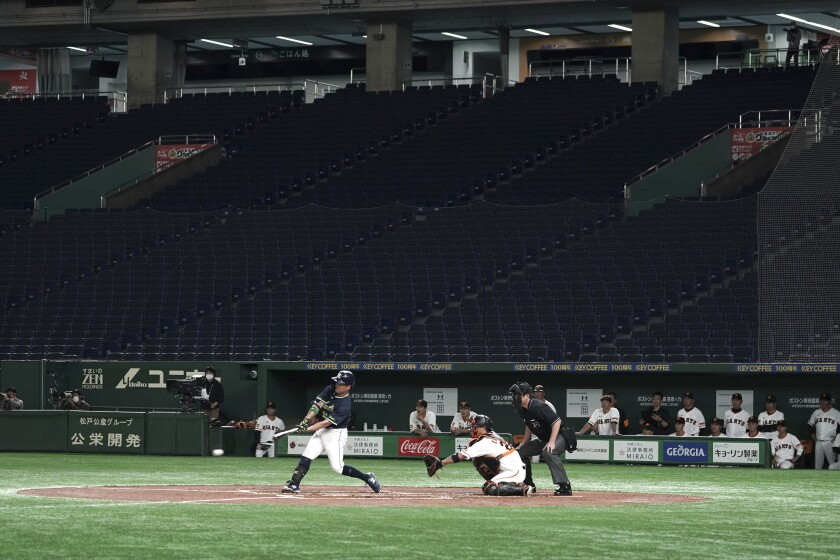 FILE - In this Feb. 29, 2020, file photo, spectators' stands are empty during a play in a preseason baseball game between the Yomiuri Giants and the Yakult Swallows at Tokyo Dome in Tokyo. The Yomiuri Giants, Japan's most famous baseball team, called off a preseason game on Wednesday, June 3, with reports that at least one player may have tested positive for the coronavirus.(AP Photo/Eugene Hoshiko, File)