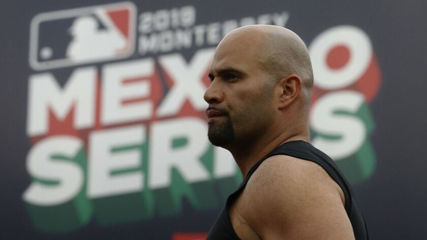 Angels' Albert Pujols walks in front a billboard during a practice session a day ahead of the Angels' two-game series against the Houston Astros, in Monterrey, Mexico.