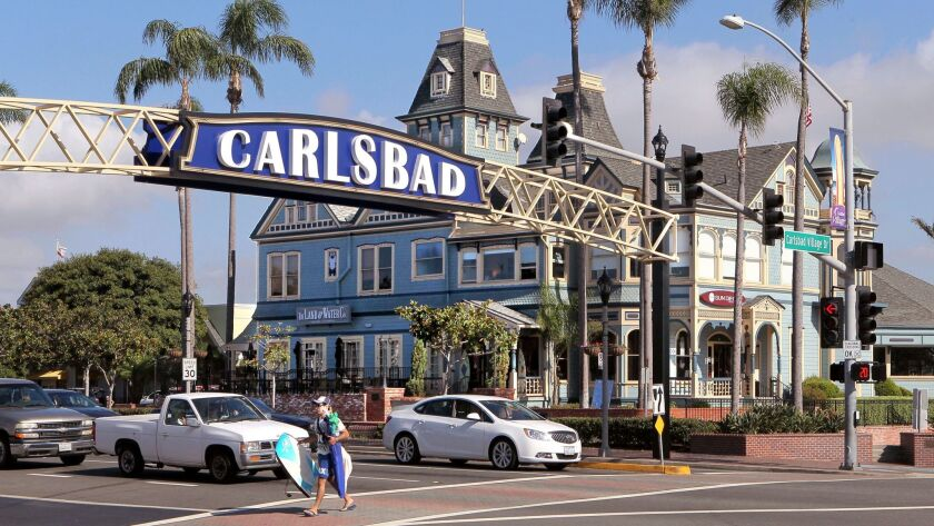 Carlsbad Blvd. traffic passes under the Carlsbad Sign. In the distance is the old Twin Inns building that now houses a restaurant and a surf/sportswear shop.