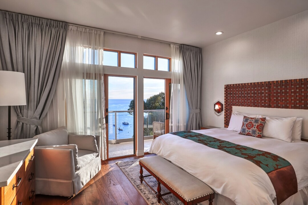A spacious hotel room with wood floors and a view of the ocean