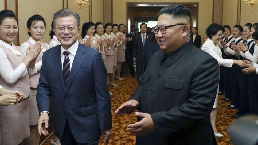South Korean President Moon Jae-in, left, and North Korean leader Kim Jong Un arrive at Paekwawon gu
