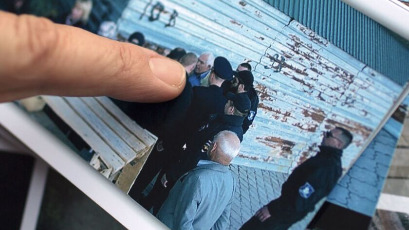 Mila Selyamieva with a photo of her husband, Alexander Strekalin, being blocked by policemen as he tried to protect his property.
