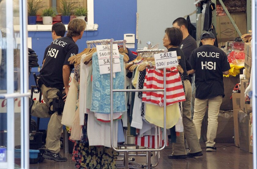 Law enforcement agents check a clothing store during a raid in the Los Angeles Fashion District Wednesday, Sept. 10, 2014. U.S. agents raided dozens of businesses in the fashion district of Los Angeles early Wednesday as part of an investigation into suspected money laundering done for Mexican drug cartels. (AP Photo/ Nick Ut )