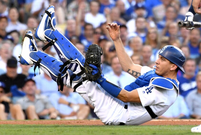 Dodgers catcher Austin Barnes falls the ground after catching a foul ball.