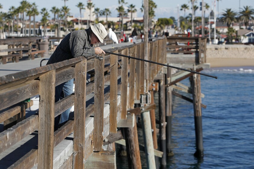 Mike Gaughan, 64, fishes for bait off the Balboa Pier in Newport Beach on Wednesday. The city of Newport Beach is considering allowing local sportfishing companies Newport Landing and Davey's Locker to place receptacles at the Balboa Pier to collect used fishing lines for recycling.