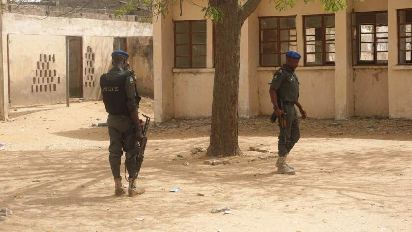 Police officers stand guard Feb. 28 at the Government Girls Technical College, where 110 girls were kidnapped by Boko Haram extremists.