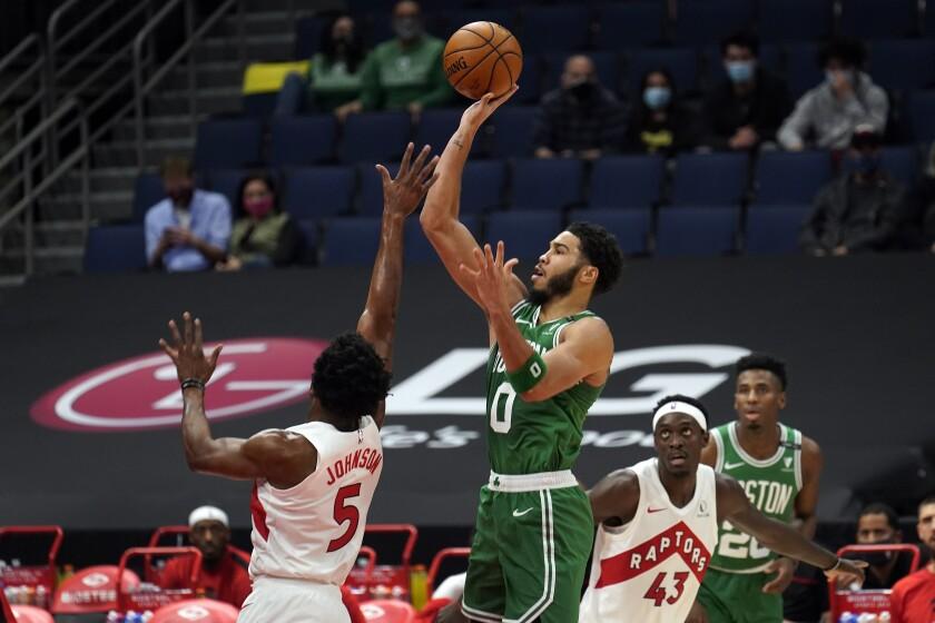 Boston Celtics forward Jayson Tatum shoots over Toronto Raptors forward Stanley Johnson.