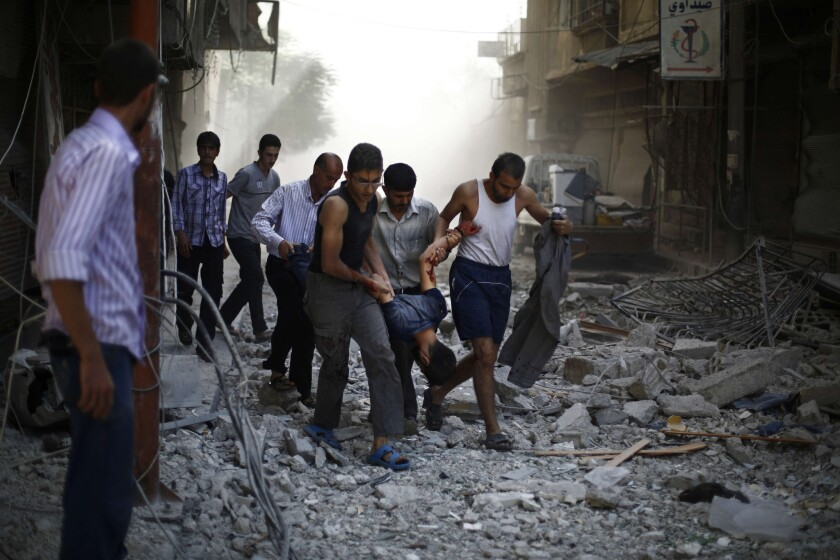 Syrians carry a wounded man after airstrikes hit the rebel-held town of Duma in 2015.