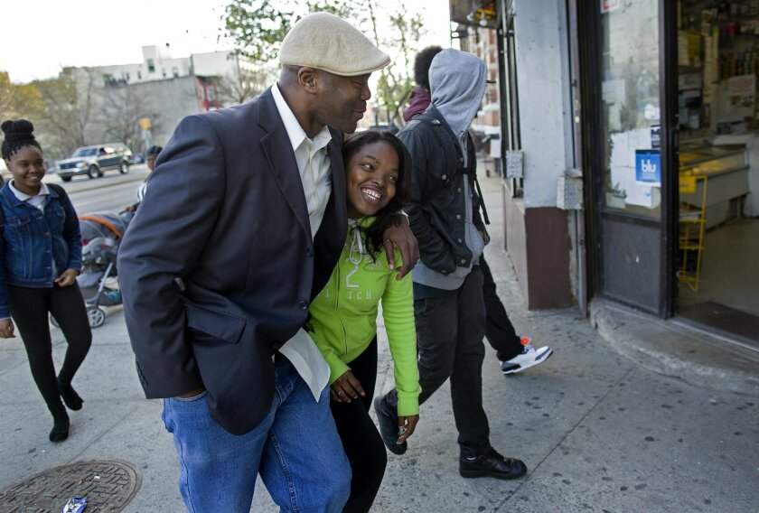 In a photograph taken Wednesday, April 23, 2014, Dr. Kai Smith, former gang member and now founder and Executive Director of GRAAFICS (Gang Diversion, reentry and Absent Father Intervention Center) jokes with student Tyasia Blair, 16, of East New York, as they walk with other GRAAFICS students  in
