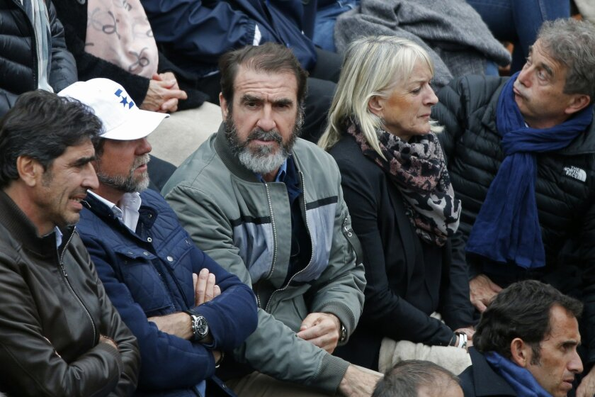Former French soccer star Eric Cantona watches the semifinal match of the French Open tennis tournament between Britain's Andy Murray and Switzerland's Stan Wawrinka at the Roland Garros stadium in Paris, France, Friday, June 3, 2016. (AP Photo/Christophe Ena)