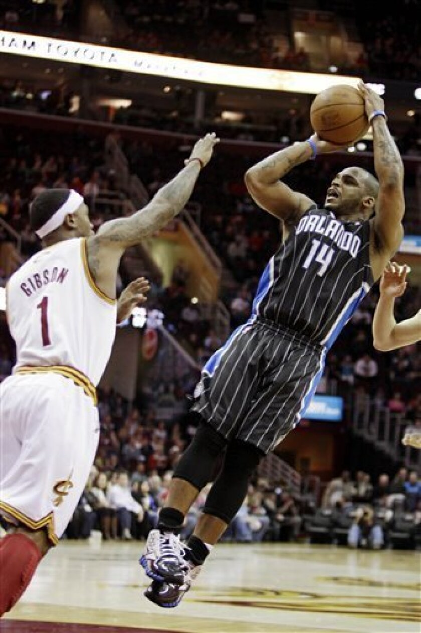 Orlando Magic's Jameer Nelson (14) shoots over Cleveland Cavaliers' Daniel Gibson (1) in the first quarter of an NBA basketball game, Monday, March 21, 2011, in Cleveland. (AP Photo/Tony Dejak)