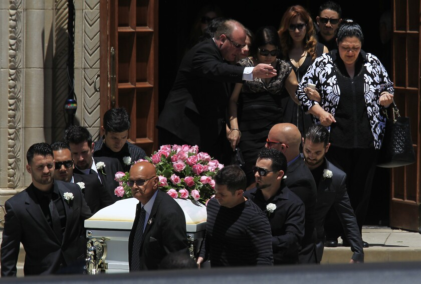 Pallbearers carry the casket of Marcela Franco as family member are escorted out following a funeral mass for Marcela and Carlos Franco at Saint Monica's Catholic Church.