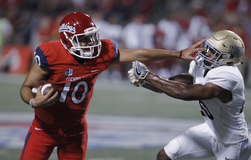 Fresno State quarterback Jorge Reyna stiff-arms Idaho's Dorian Clark during a game in September 2018.