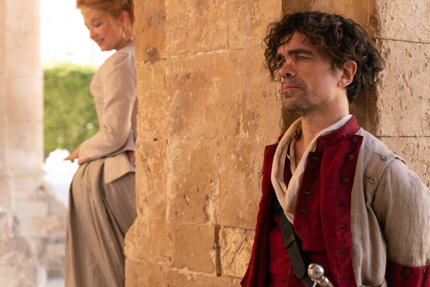 Peter Dinklage, in period costume and sword, stands on the other side of a pillar from Haley Bennett, in period gown.