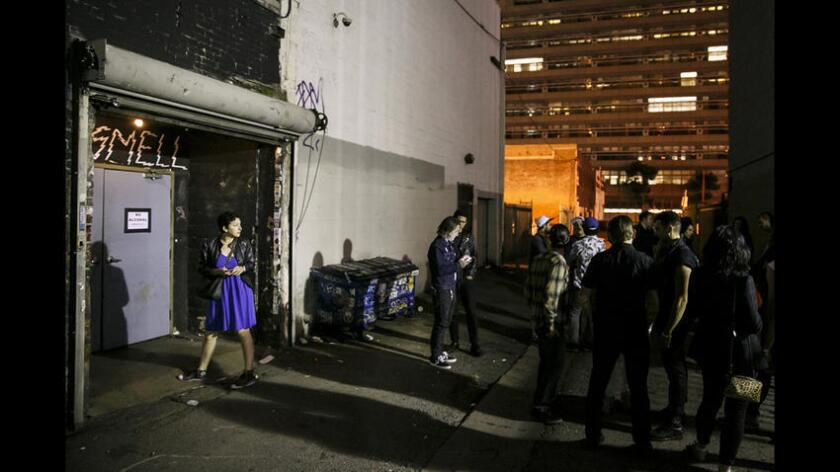 Patrons take a break outside the alleyway entrance at the Smell in downtown Los Angeles.
