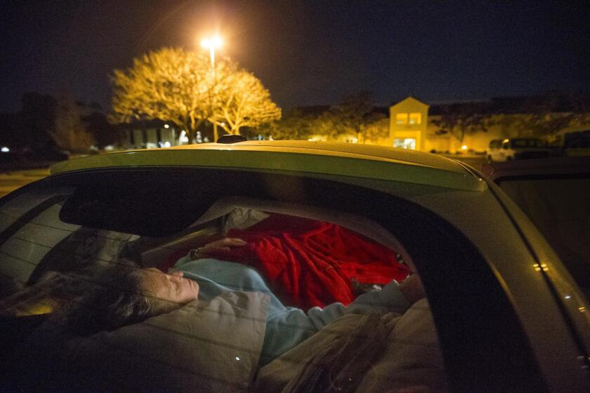 A homeless senior citizen living in her PT Cruiser tucks into an air mattress to sleep with her two dogs.
