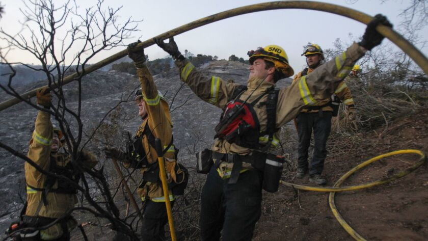 Firefighters work to get a hose over some brush as they manuever on charred hillls.