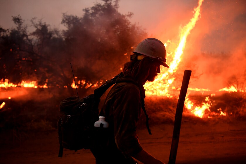 A firefighter helps to set counter-fires as the El Dorado fire approaches in Yucaipa on Sept. 7.