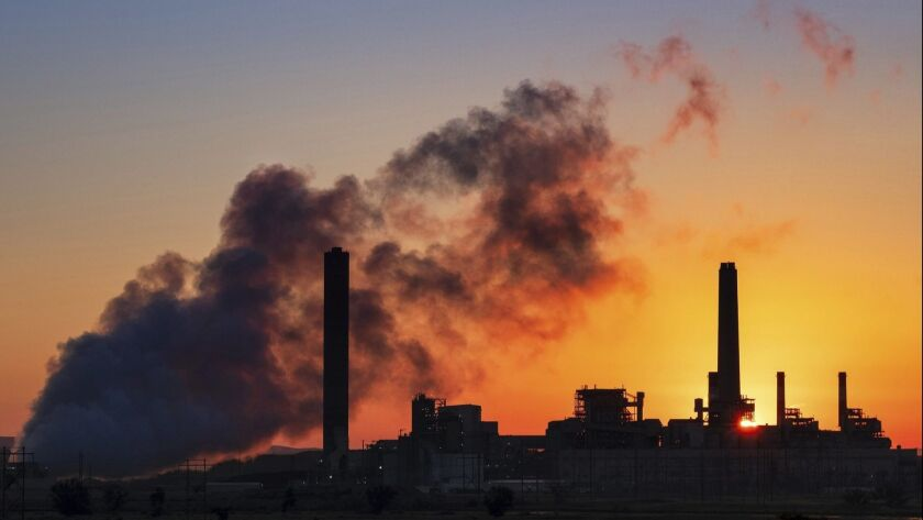 In this July 27, 2018, photo the Dave Johnson coal-fired power plant is silhouetted against the morn
