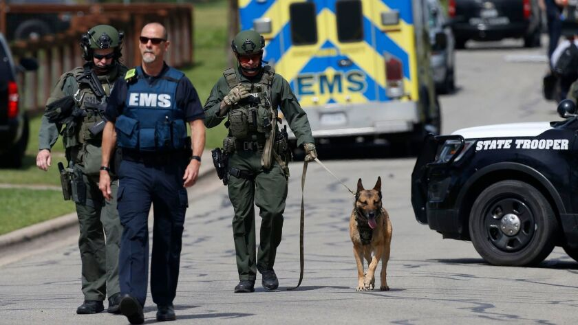 Police walk through a Pflugerville, Texas, neighborhood as the FBI investigates the home of the Austin serial bomber.