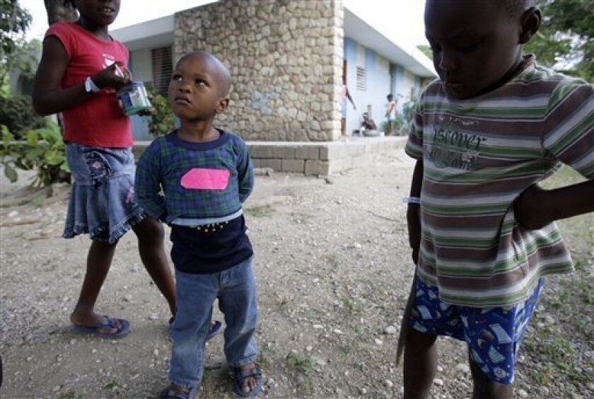 A boy, with a pink tape on his shirt that previously had his name written on it, and who was part of the group of children that U.S. Baptists were trying to take out of Haiti, looks at other kids playing at an orphanage run by Austrian-based SOS Children's Villages in Port-au-Prince, Sunday, Jan. 31, 2010. Ten Americans were detained by Haitian police on Saturday as they tried to bus 33 children across the border into the Dominican Republic, allegedly without proper documents. (AP Photo/Andres Leighton)