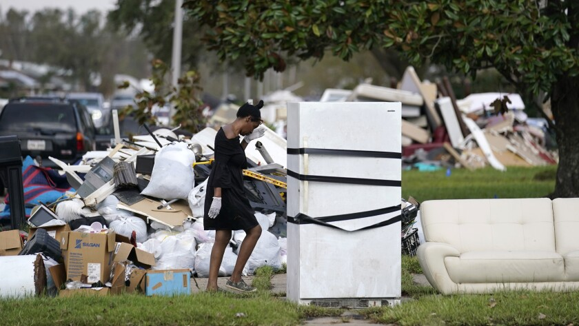 A woman walks among piles of debris, a couch and a refrigerator outside.