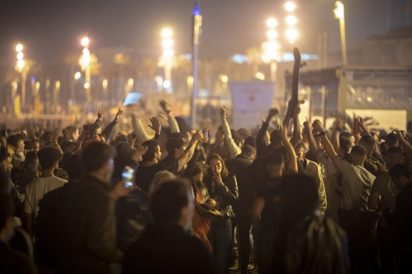 People crowded and dance on the beach in Barcelona, Spain, Sunday, May 9, 2021. Barcelona residents were euphoric as the clock stroke midnight, ending a six-month-long national state of emergency and consequently, the local curfew. Spain is relaxing overall measures to contain the coronavirus this weekend, allowing residents to travel across regions, but some regional chiefs are complaining that a patchwork of approaches will replace the six-month-long national state of emergency that ends at midnight on Saturday. (AP Photo/Emilio Morenatti)