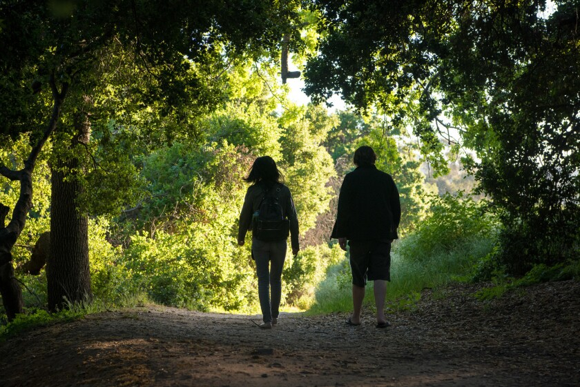 Yuan and Brandon Ryan, of Reseda, hike through an oak grove by a gully at Corriganville Park.