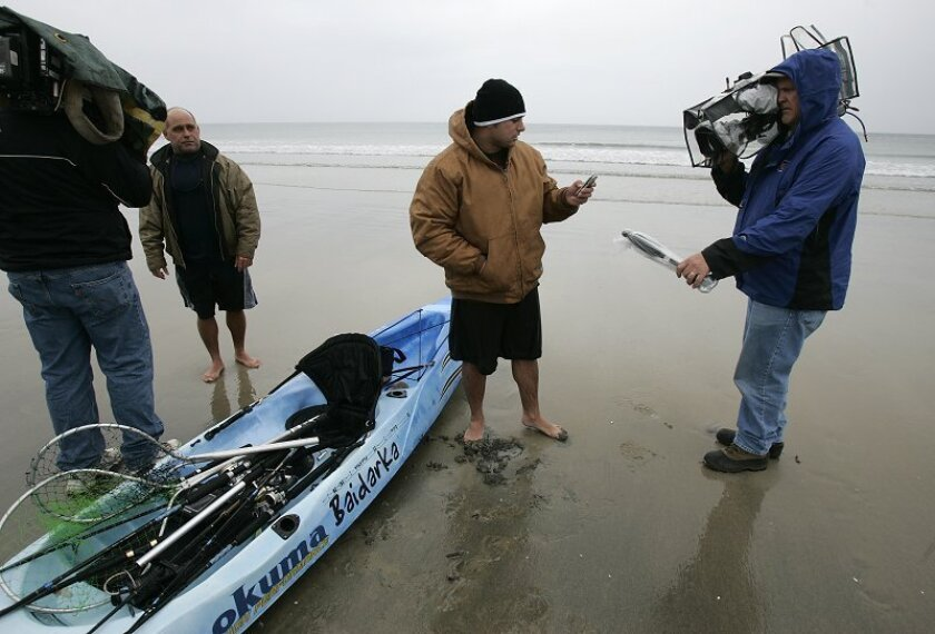 David A. McClurg (right) talks with TV cameramen as his dad, David(left), watches, after they were rescued a couple of miles off La Jolla Shores  on Monday morning. The two were kayak fishing when the wind picked up and rolled  the younger McClurg over into the water. They used a cell phone to call