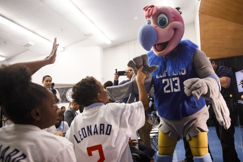 "Clippers mascot ""Chuck"" high fives students before Kawhi Leonard gives backpacks away to students at One Hundred Seventh Street Elementary School on Tuesday in the Watts neighborhood of Los Angeles."
