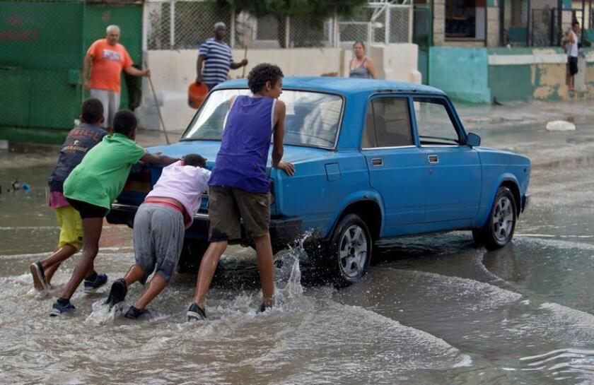 Youngsters push a car through floodwaters that have begun to subside from a street in Havana on Dec. 22, 2018, following a powerful storm affecting the Cuban capital and the western part of the island. EFE-EPA/Yander Zamora