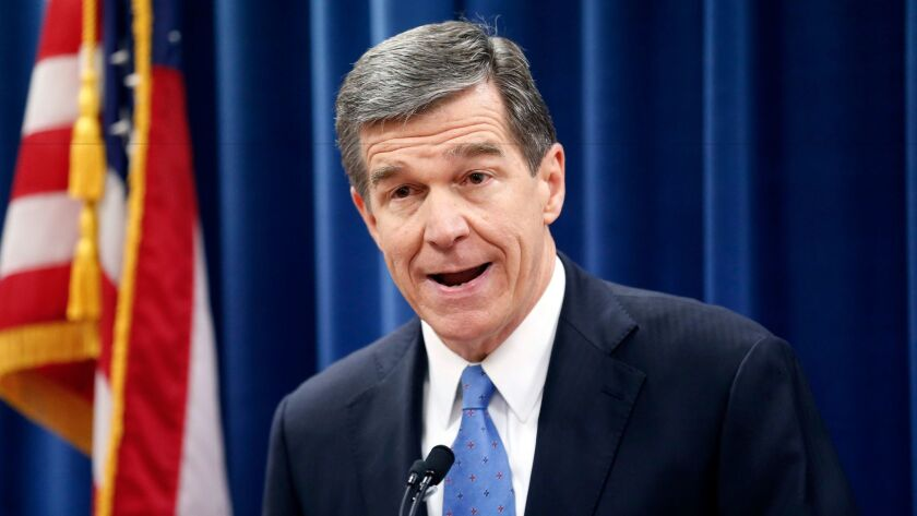 Roy Cooper, then governor-elect of North Carolina, speaks in December at a news conference criticizing Republican efforts to cut the power of his office.