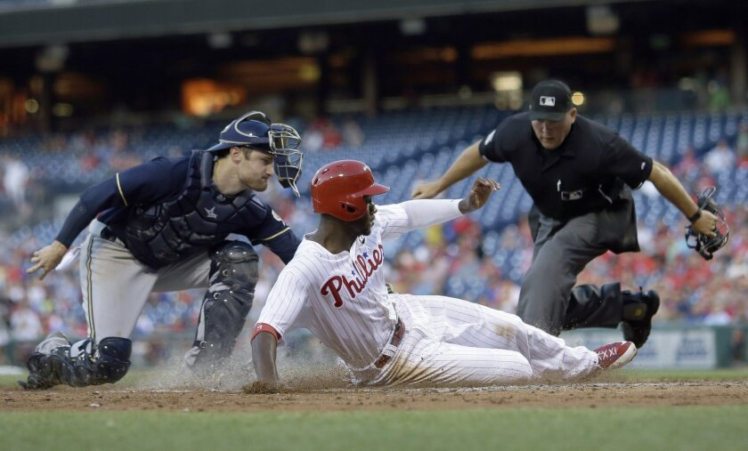 Philadelphia Phillies' Domonic Brown, center, is tagged out by Milwaukee Brewers catcher Jonathan Lucroy, left, as umpire Mark Carlson looks on after Brown tried to score on a double by Cody Asche during the third inning of a baseball game, Monday, June 29, 2015, in Philadelphia. (AP Photo/Matt Slo