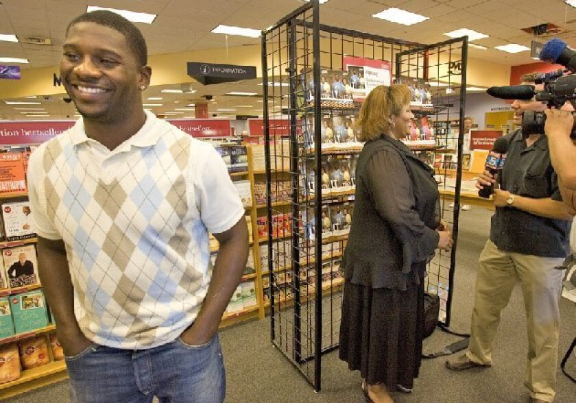 LaDainian Tomlinson smiles as his mother, Loreane, was interviewed yesterday about her new book. (Earnie Grafton / Union-Tribune)
