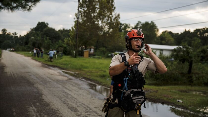 Master Sgt. Adam Vanhaaster signals to his crew as he follows up on an evacuation call in a neighbor