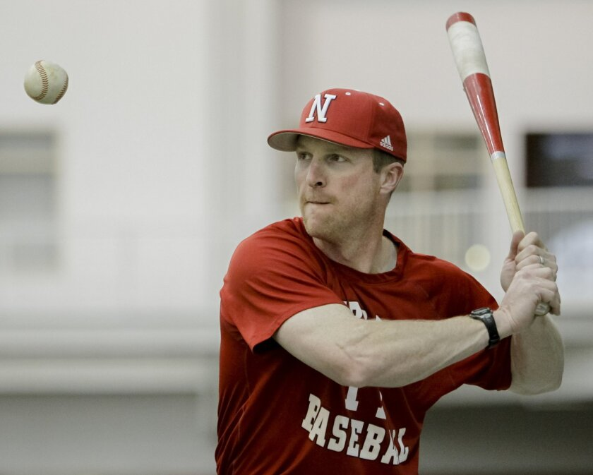 FILE - In this Feb. 28, 2012, file photo, Nebraska coach Darin Erstad hits balls during NCAA college baseball practice in Lincoln, Neb. A few days after Erstad interviewed for the Los Angeles Dodgers manager's job, he was working with a small group of his Nebraska players in the batting cage when he had an epiphany. Nebraska is where he belongs. (AP Photo/Nati Harnik, File)