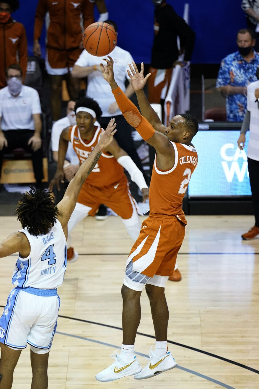 Texas guard Matt Coleman III (2) shoots for the winning basket over North Carolina guard R.J. Davis (4) in the second half an NCAA college basketball game for the championship of the Maui Invitational, Wednesday, Dec. 2, 2020, in Asheville, N.C. Texas won 69-67. Coleman was awarded the MVP. (AP Photo/Kathy Kmonicek)