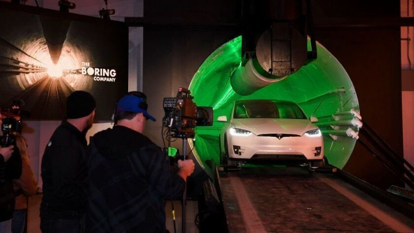 Elon Musk arrives in a modified Tesla Model X during an unveiling of the Hawthorne test tunnel on Dec. 18.