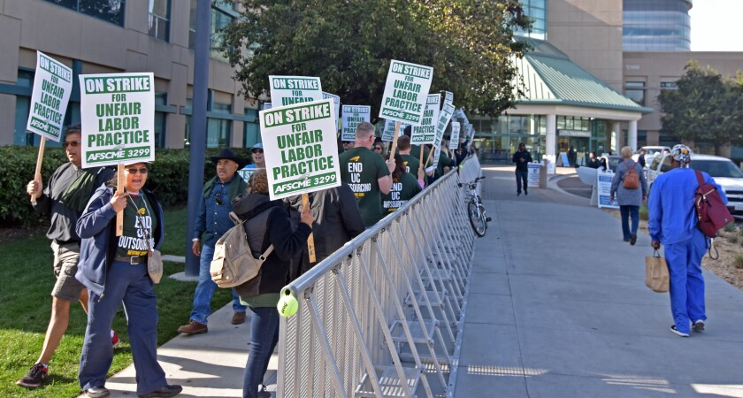 Members of AFSCME Local 3299 picket outside Jacobs Medical Center Wednesday during a one-day strike over long-standing anger regarding university outsourcing practices.
