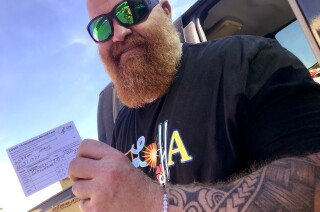 A tattooed and bearded Shane Curran flashes a smile and his vaccine card after receiving his Johnson & Johnson vaccine