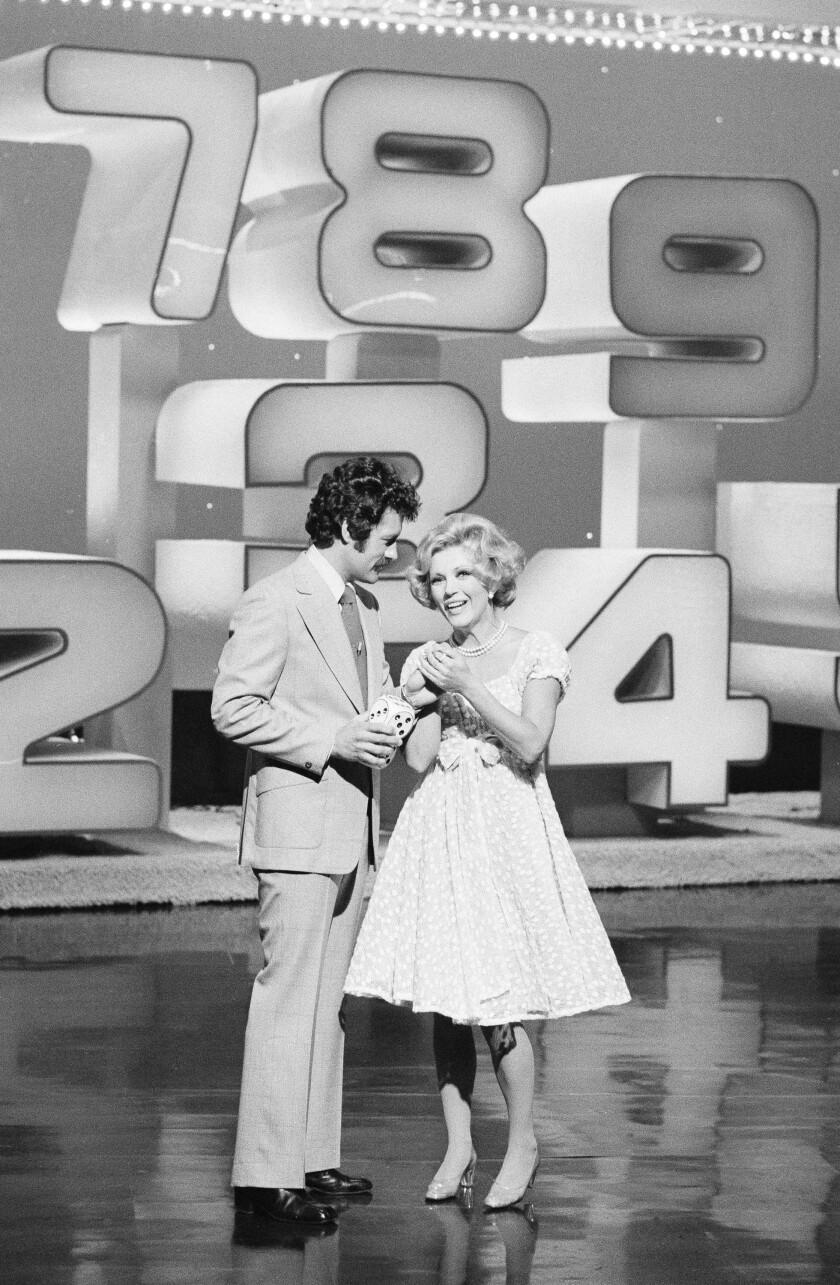"""Black-and-white photo of Alex Trebek and Ruta Lee on the set of the 1970s game show """"High Rollers."""""""