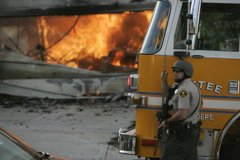 San Diego County Sheriff's deputies armed with rifles cordoned off a burning home in Santee, while firefighters battled the blaze.