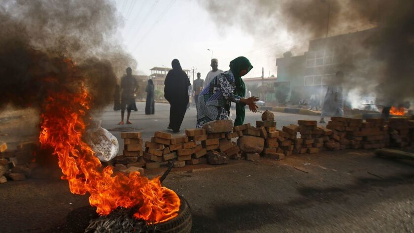 Using burning tires and pieces of pavement, Sudanese protesters close a street outside Khartoum's army headquarters on Monday.